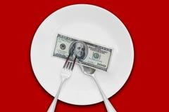 Cientos billetes de dólar en la placa que se comerá Foto de archivo