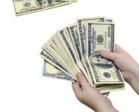 Cientos billetes de dólar en manos en un blanco aislaron el fondo Fotografía de archivo libre de regalías