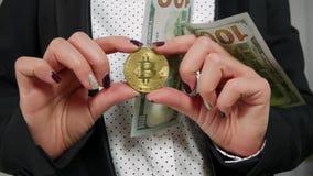 Cientos billetes de dólar que caen con Bitcoin que llevan a cabo las manos almacen de video