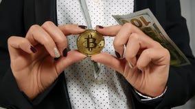 Cientos billetes de dólar que caen con Bitcoin que llevan a cabo las manos Imagenes de archivo