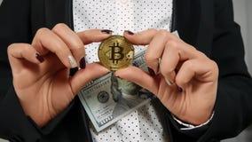Cientos billetes de dólar que caen con Bitcoin que llevan a cabo las manos Foto de archivo libre de regalías