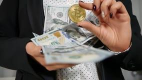 Cientos billetes de dólar que caen en la mano con Bitcoin Foto de archivo