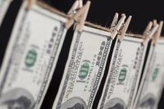 Cientos billetes de dólar que cuelgan de cuerda para tender la ropa en fondo oscuro Imágenes de archivo libres de regalías