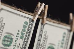 Cientos billetes de dólar que cuelgan de cuerda para tender la ropa en fondo oscuro Imagen de archivo