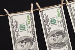 Cientos billetes de dólar que cuelgan de cuerda para tender la ropa en fondo oscuro Fotografía de archivo