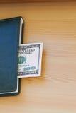 Cientos billetes de dólar que mienten en el cuaderno Fotografía de archivo