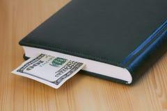 Cientos billetes de dólar que mienten en el cuaderno Imagen de archivo libre de regalías