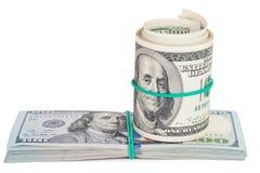 Cientos billetes de dólar rodados para arriba con el rubberband Fotos de archivo