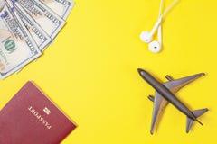 Cientos billetes de d?lar, aeroplano, auriculares, pasaporte extranjero en fondo de papel amarillo brillante Copie el espacio fotos de archivo libres de regalías