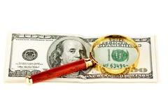 Cientos cuentas de dólar bajo una lupa Fotografía de archivo libre de regalías