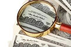 Cientos cuentas de dólar bajo una lupa Imagenes de archivo