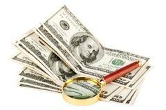 Cientos cuentas de dólar bajo una lupa Imagen de archivo