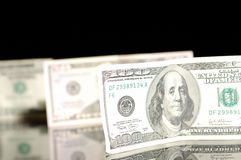 Cientos cuentas de dólar en el fondo negro. Fotos de archivo libres de regalías