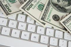 Cientos cuentas de dólar en el teclado de ordenador Imagen de archivo libre de regalías