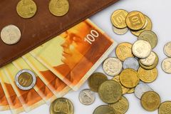 Cientos cuentas de los shekels rodeadas por muchas monedas en un fondo blanco fotos de archivo