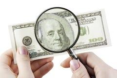 Cientos dólares bajo la lupa Foto de archivo libre de regalías