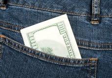 Cientos dólares de billete de banco en el cadera-bolsillo de pantalones vaqueros Foto de archivo