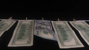 Cientos dólares de billetes de banco pesan en una cuerda en fila con las pinzas T almacen de metraje de vídeo