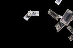 Cientos dólares de billetes de banco vuelan en fondo negro Concepto de la lluvia del dinero imagenes de archivo