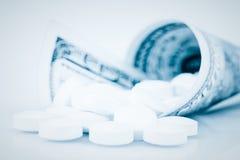 Cientos dólares de cuenta que contiene las píldoras blancas Fotografía de archivo libre de regalías