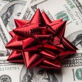 Cientos dólares de EE. UU. de cuentas con el arco de los días de fiesta Fotografía de archivo