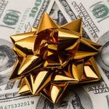 Cientos dólares de EE. UU. de cuentas con el arco de los días de fiesta Imagen de archivo libre de regalías