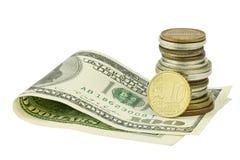 Cientos dólares debajo de monedas con el centavo euro Imagen de archivo libre de regalías