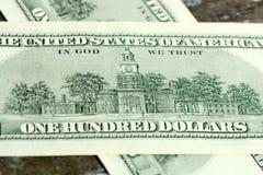 Cientos dólares en la madera Imagen de archivo