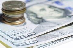 Cientos dólares y cierres de la pila de la moneda para arriba con el foco selectivo Imagen de archivo libre de regalías