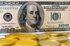 Cientos dólares y oros Foto de archivo libre de regalías