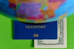 Cientos dólares y un pasaporte en un fondo verde con un mapa del globo fotos de archivo libres de regalías