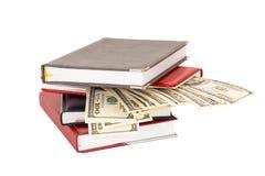 Cientos dineros de los billetes de dólar y una pila de cuadernos Fotografía de archivo