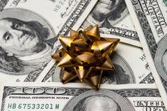 Cientos dólares de EE. UU. de cuentas con el arco de los días de fiesta Foto de archivo libre de regalías