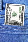 Cientos dólares en bolsillo de los pantalones vaqueros Imagen de archivo libre de regalías