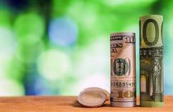 Cientos euros y cientos billetes de banco rodados dólar de EE. UU. de las cuentas Foto de archivo