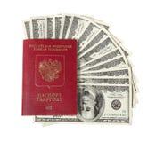 Cientos ventiladores de los billetes de dólar con un pasaporte Fotos de archivo libres de regalías