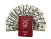 Cientos ventiladores de los billetes de dólar con un pasaporte Imagen de archivo