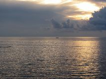 Ciepły denny zmierzch z małą łodzią rybacką na wodzie Giganta cumulonimbusu chmury w nieba i słońca promieniach Tuscany, Ital Fotografia Stock
