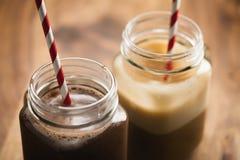 Ciepły kakao i kawa w słojów kubkach na drewnianym stole Obrazy Royalty Free