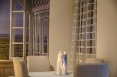 Ciepli blaski świecy na szklanym bielu stole zdjęcie stock