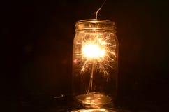 Cierge magique de feux d'artifice de nuit brûlant à l'intérieur du pot en verre Photographie stock libre de droits