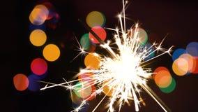Cierge magique de Noël brûlant sur un fond d'arbre de Noël avec les lumières colorées de bokeh et de Noël banque de vidéos