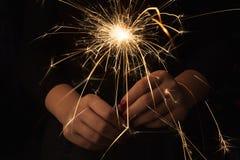 Cierge magique de partie de nouvelle année dans des mains femelles sur le fond noir Photographie stock