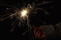 Cierge magique de partie de nouvelle année dans la main femelle sur le fond noir Image libre de droits
