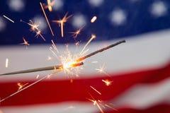 Cierges magiques brûlant sur le fond de drapeau américain Image stock