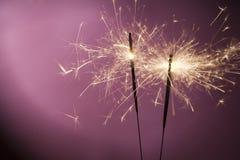 Cierges magiques brûlants sur le fond rose Photographie stock