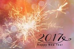 Cierges magiques contre un contexte rose avec le bokeh Citation de la bonne année 2017 Image stock
