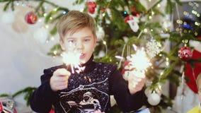 Cierges magiques heureux de brûlure d'enfant parmi des lumières et des guirlandes de bokeh sur un arbre de Noël Mouvement lent 38 banque de vidéos