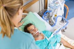 Cierpliwa Patrzeje pielęgniarka Gdy Przystosowywa Jego poduszkę fotografia stock