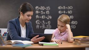 Cierpliwy dama nauczyciel wyjaśnia temat na pastylce, uczeń no rozumie zbiory